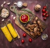 Os reforços roasted deliciosos do cordeiro com molho picante e ervas em uma placa de corte com milho e fundo rústico de madeira d Imagem de Stock