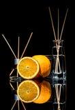 Os refrogeradores de ar com frutos alaranjados scent no frascos de vidro bonitos com varas e o alaranjado inteiro e uma fatia de  fotos de stock royalty free