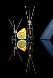Os refrogeradores de ar com limão scent no frascos de vidro bonitos com varas e o limão inteiro e uma fatia de limão com reflexão foto de stock