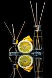 Os refrogeradores de ar com limão scent no frascos de vidro bonitos com varas e o limão inteiro e uma fatia de limão com reflexão fotografia de stock royalty free