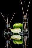 Os refrogeradores de ar com maçã verde scent no frascos de vidro bonitos com varas e a maçã verde inteira e uma fatia de maçã fotografia de stock