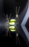 Os refrogeradores de ar com maçã verde scent no frascos de vidro bonitos com varas e a maçã verde inteira e uma fatia de maçã fotografia de stock royalty free