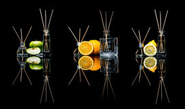 Os refrogeradores de ar em um vidro rangem com as varas e o limão, maçã verde e laranja com reflexão isolados em um preto Imagem de Stock Royalty Free