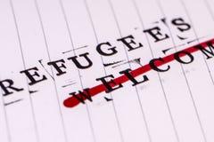 Os refugiados dão boas-vindas ao texto do strikethrough no papel fotografia de stock