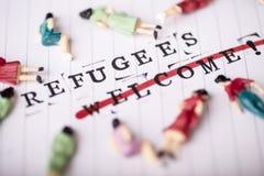Os refugiados dão boas-vindas ao texto do strikethrough no papel fotos de stock royalty free