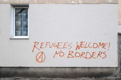 Os refugiados dão boas-vindas a grafittis dentro na parede em Varsóvia foto de stock