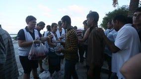 Os refugiados da guerra estão em uma fila para receber a ajuda humanitária - água e maçãs filme