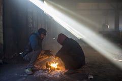 Os refugiados tentam aquecer-se pelo fogo em um hangar abandonado Fotografia de Stock Royalty Free