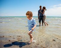 Os relógios dos pares como o filho andam longe da água Fotografia de Stock