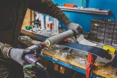 Os reparos de um trabalhador do homem no esqui prestam serviços de manutenção à oficina a superfície de deslizamento dos esquis,  foto de stock royalty free
