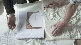Os restauradores dos mestres do homem que trabalham na restauração projetam-se na tabela no escritório moderno filme