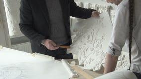 Os restauradores experientes dos arquitetos estão funcionando com as decorações da gipsita na oficina moderna filme