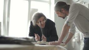 Os restauradores masculinos dos arquitetos estão funcionando no projeto na tabela na oficina moderna