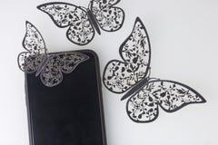 Os restos do smartphone em uma superfície branca Em torno dele ornamento das borboletas, corte da folha Foto de Stock Royalty Free