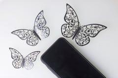 Os restos do smartphone em uma superfície branca Em torno dele ornamento das borboletas, corte da folha Imagem de Stock