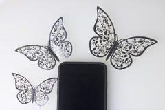 Os restos do smartphone em uma superfície branca Em torno dele ornamento das borboletas, corte da folha Imagens de Stock