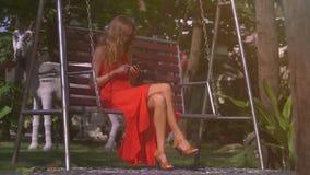 Os restos louros da menina no jardim balançam no parque tropical video estoque