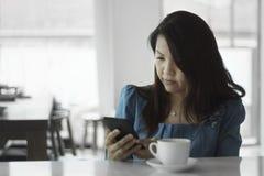 Os retratos fêmeas asiáticos das mulheres olham o telefone esperto Imagem de Stock