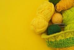Os revestimentos amarelos e verdes das lãs encontram-se na tabela O passatempo favorito está fazendo malha fotografia de stock royalty free
