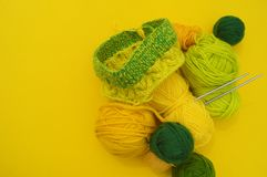 Os revestimentos amarelos e verdes das lãs encontram-se na tabela O passatempo favorito está fazendo malha imagem de stock royalty free