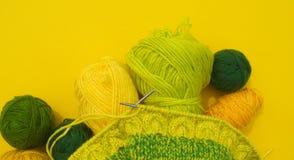 Os revestimentos amarelos e verdes das lãs encontram-se na tabela O passatempo favorito está fazendo malha fotos de stock