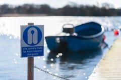 Os revestimentos de vida devem ser vestidos além deste sinal de aviso do ponto em Hornsea mero imagem de stock