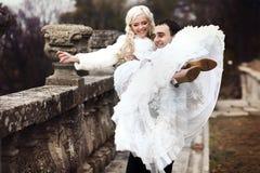 Os ricos preparam e a grama da parede do fundo do huggingoutdoor da noiva aquece a fotos de stock royalty free