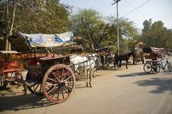 Os riquexós e os carros com cavalos estão na rua na Índia e em passageiros de espera imagem de stock