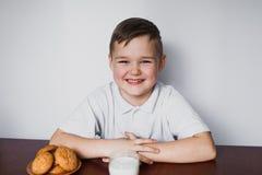 Os risos do menino Perto das cookies e do leite da tabela Fotografia de Stock