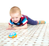Os risos louros pequenos do menino, encontrando-se em um assoalho e em uma observação Imagens de Stock Royalty Free