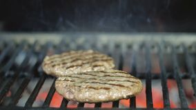 Os rissóis do Hamburger estão preparando-se para um partido do assado em um fim de semana festivo na grade do josper video estoque
