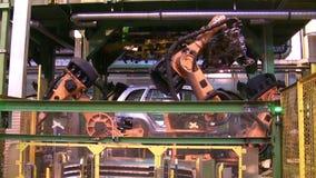 Os robôs soldam as peças do carro na linha de produção na fábrica video estoque