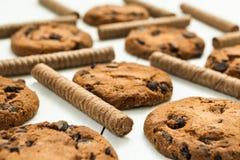 Os rolos da bolacha do chocolate e cozeram recentemente cookies caseiros do chocolate em uma tabela de madeira branca fotografia de stock