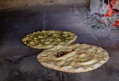 Os rolos de pão italiano são cozidos em um forno de pedra na perspectiva do fogo fotografia de stock