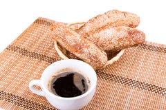 Rolos de pão recentemente cozidos com sésamo com chávena de café Foto de Stock Royalty Free