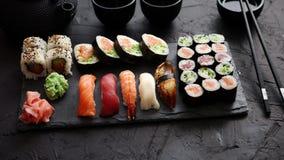 Os rolos de sushi ajustados com os peixes dos salmões e de atum serviram na placa de pedra preta video estoque