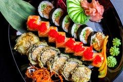 Os rolos de sushi ajustados serviram na placa de vidro no fundo escuro Fotografia de Stock Royalty Free