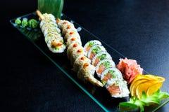 Os rolos de sushi ajustados serviram na placa de vidro no fundo escuro Foto de Stock Royalty Free