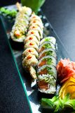 Os rolos de sushi ajustados serviram na placa de vidro no fundo escuro Imagens de Stock Royalty Free