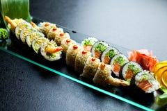 Os rolos de sushi ajustados serviram na placa de vidro no fundo escuro Fotografia de Stock