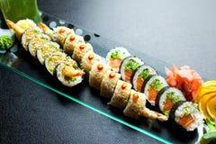 Os rolos de sushi ajustados serviram na placa de vidro no fundo escuro Imagem de Stock