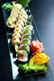 Os rolos de sushi ajustados serviram na placa de vidro no fundo escuro Imagens de Stock