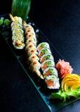 Os rolos de sushi ajustados serviram na placa de vidro no fundo escuro Fotos de Stock