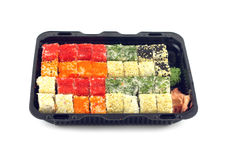 Os rolos de sushi com ovas Masago dos peixes encontram-se no recipiente plástico isolado Foto de Stock