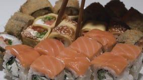 Os rolos de sushi em um rolo de sushi do close-up da placa com tomada da panqueca do ovo colam slowmotion vídeos de arquivo