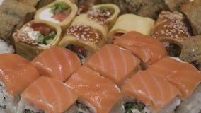 Os rolos de sushi em uma câmera do close-up da opinião superior da placa movem da esquerda para a direita slowmotion filme