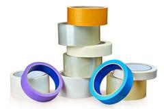 Os rolos diferentes da fita adesiva encontram-se na tabela, fundo branco Imagens de Stock