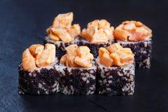 Os rolos do sushi cobriram com o caviar salmon e preto torched servido Fotos de Stock