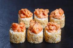 Os rolos do sushi cobriram com os salmões torched servidos em precários de pedra pretos Imagens de Stock