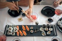 Os rolos do sushi e do nigiri serviram com o gengibre japonês no almoço com Fotos de Stock Royalty Free